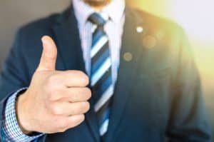 Man wearing suit giving thumbs up