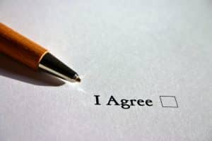 Photo of pen next to I Agree check box on paper