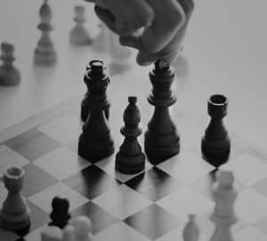 Black and white photo of person moving chess piece