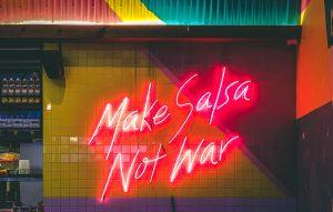 """Neon sign reading """"Make Salsa Not War"""""""