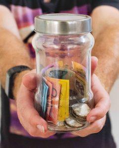 Jar of australian money in man's hands