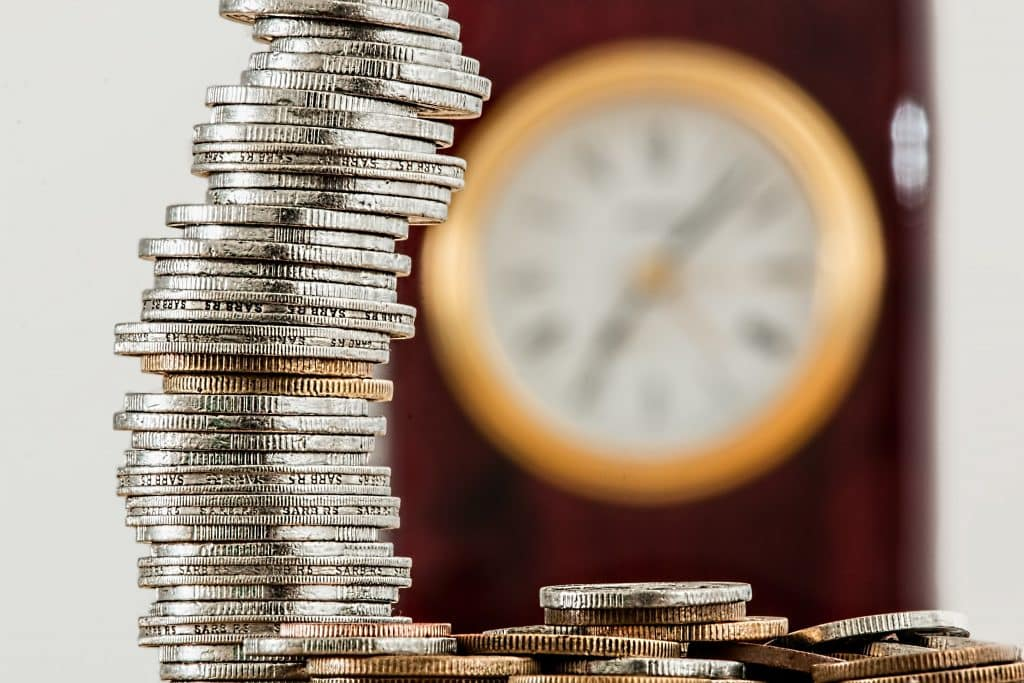 coins in foreground clock in background