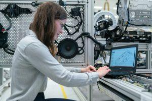 Engineer in workshop looking at design on laptop