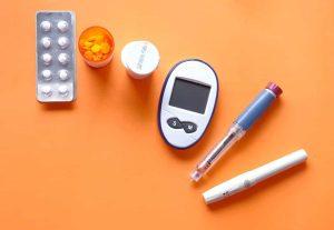 diabetes devices flatlay on orange background